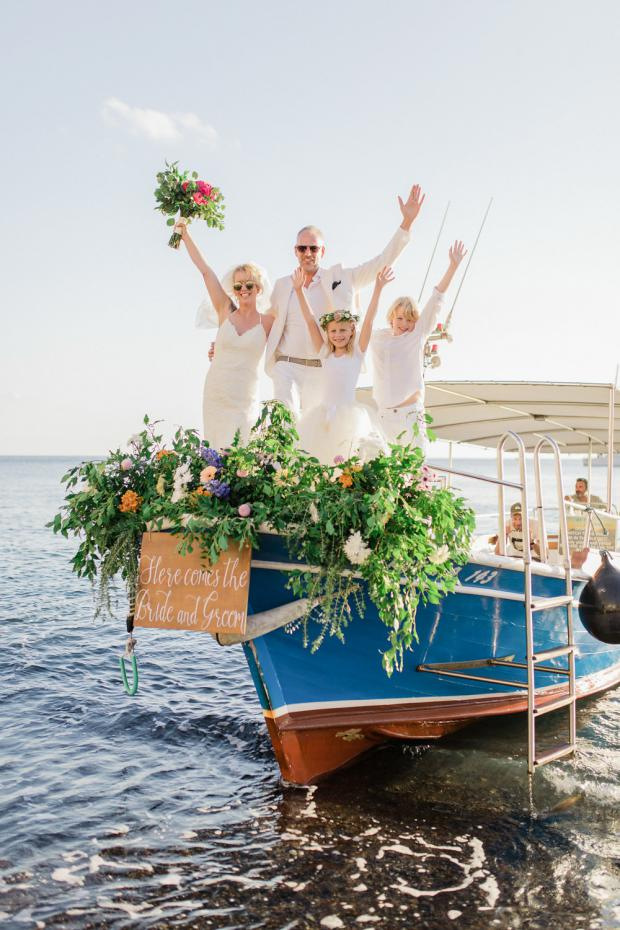 Beach wedding in Greece-Bride and groom arrive on a boat