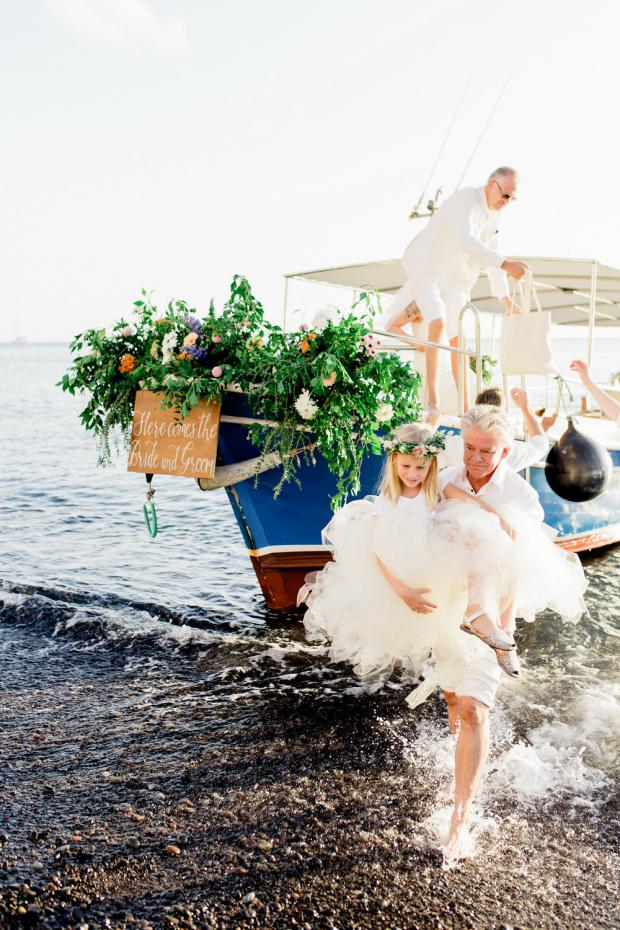 Bride and groom  arrive on a decorated with flowers boat