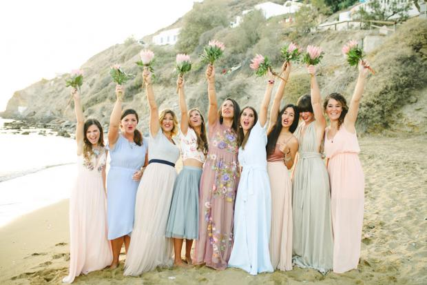 Bridesmaids in mismatched dresses and king protea bouquets