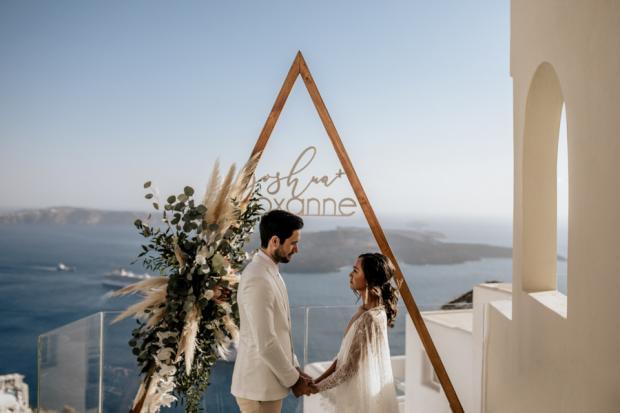 Bohemian & modern wedding in Santorini- triangle arch